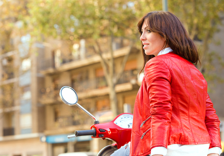 motobike: Young girl with red jacket riding on her red motorbike Stock Photo
