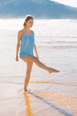 young woman dancing in the sea shore at dawn