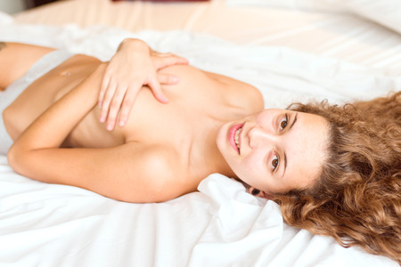unclothed: Young natural woman lying on her bed with little clothes, in the morning