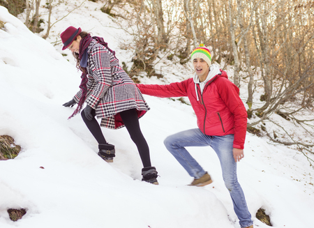 escalation: Couple walking in the snow in a forest glade