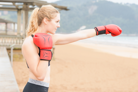 boxing day: Young girl trains boxing a cloudy and rainy day on the beach, next to the water