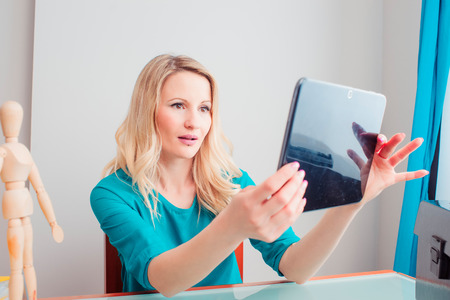 Young single woman checks her tablet in a room of her house