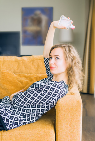Portrait of young and sensual housewife lying on a sofa in her house