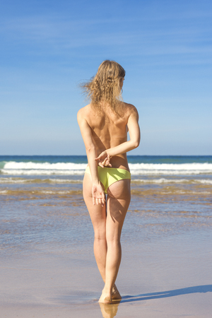 Young woman in toples backs posing facing the sea at sunset