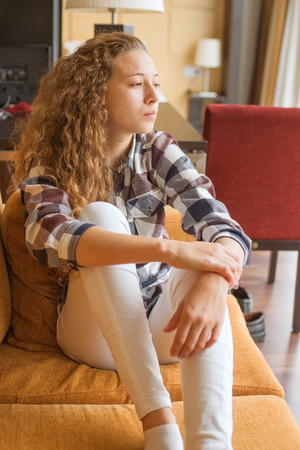 Young woman distracted on the sofa of her house on a quiet day