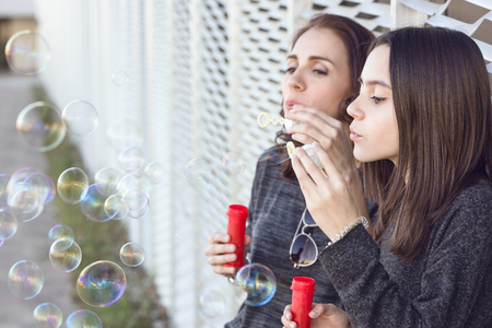 Mother and daughter blowing bubbles on a street a spring day
