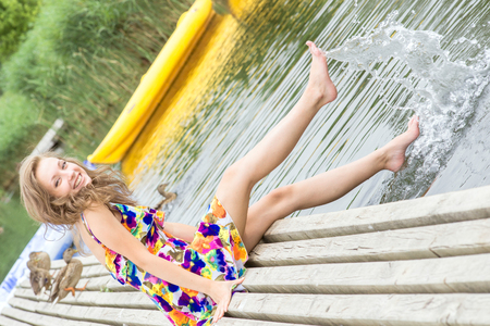 Jong meisje spat water met haar voeten op de pier Stockfoto