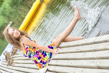 Young girl splashes water with her feet on the pier