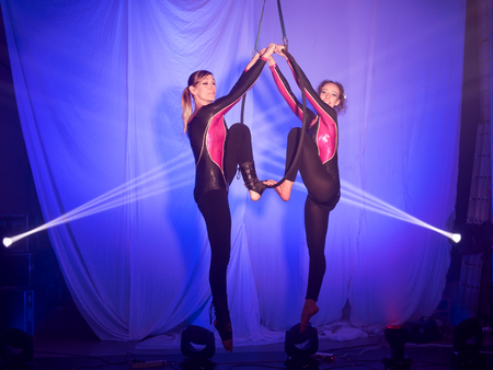 Two acrobats women do exercises hanging from hoop in front of a blue background