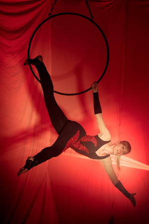 Acrobat woman doing exercises hanging on the hoop in front of a red background Stock Photo