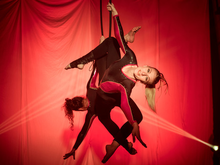 Two acrobats women do exercises hanging on the hoop in front of a red background Stock Photo