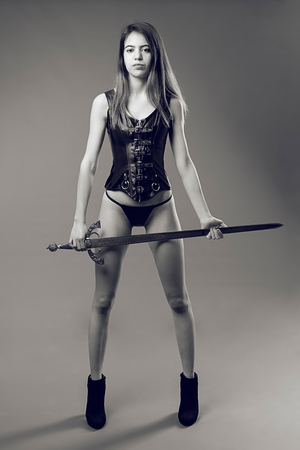 characterization: Attractive girl poses with leather corset and medieval sword in the studio