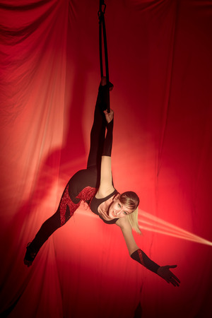 lighting background: Acrobat woman doing exercises hanging on the hoop in front of a red background Stock Photo