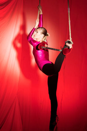 Acrobat woman doing exercises hanging from hoop in front of a red background