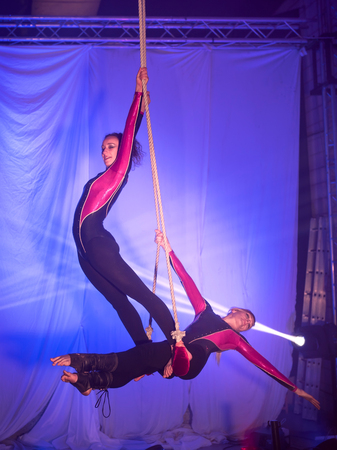 Two acrobats women do exercises hanging on the trapeze in front of a blue background