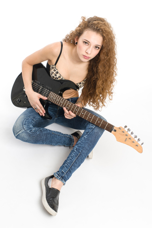 Young guitarist girl posing on white background;
