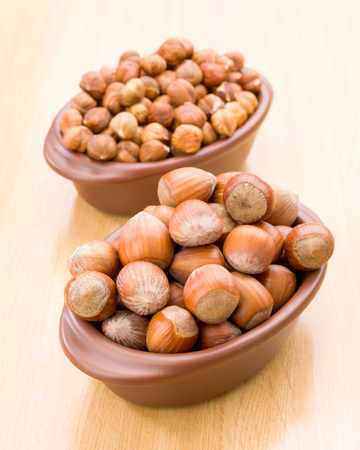 hazelnuts in clay bowl on wooden background Stock Photo
