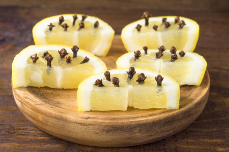 slices of lemon with clove spice, on rustic wood