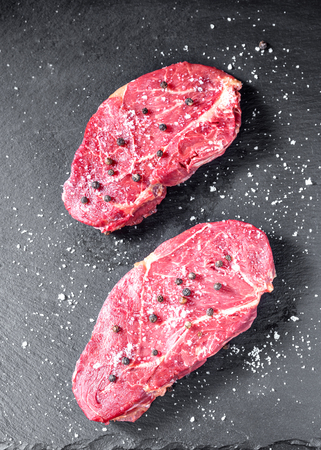 uncooked horse meat steaks on black stone