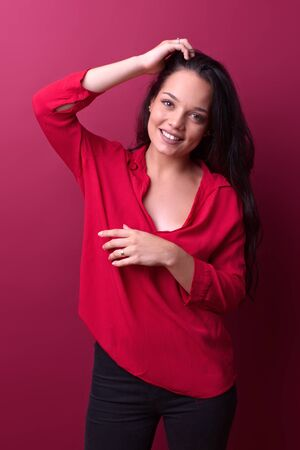 cheerful young girl removes her hair in front of a red background
