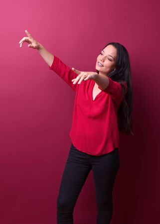 cheerful girl gestures in front of a red background