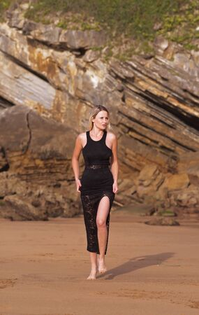 young woman in black dress walks on the sand of the beach with golden sunset light