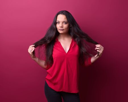 young girl removes her hair in front of a red background