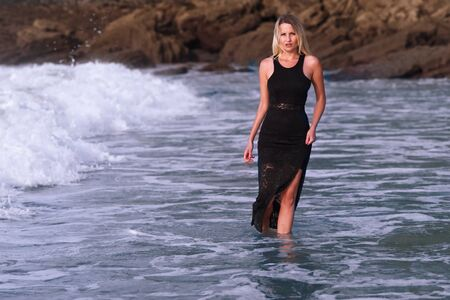 young woman in black dress plunges into the raging waves of the sea 写真素材 - 128725072