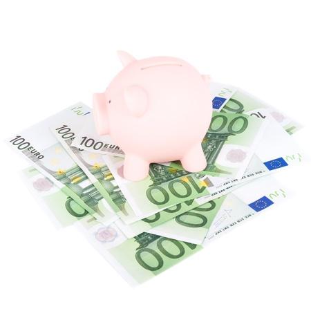 coinbank: Piggy coinbank on a hundred euro banknotes. Stock Photo