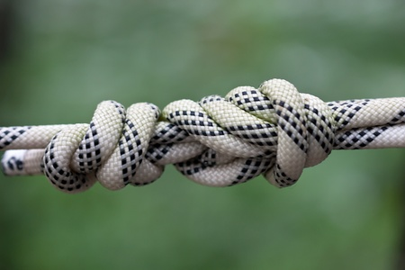 Close-up photo of rope with knot tied on green background  photo