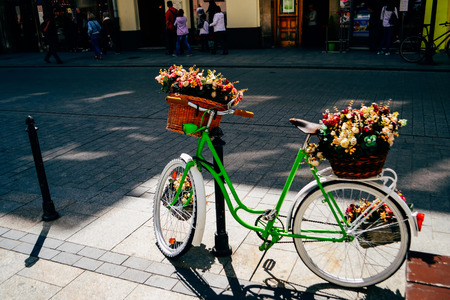green bicycle standing on the street - some flowers in the basket