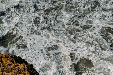 Sea water surface with white foam and waves pattern
