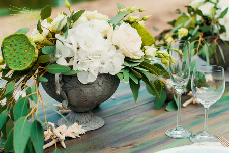 Bouquet of flowers and greenery is on the wedding table in the banquet area