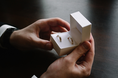 Man's hands holding a white box with a wedding rings. Standard-Bild