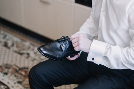 Groom's morning. Wedding accessories. Shoes. The groom ties the shoelaces on his shoes