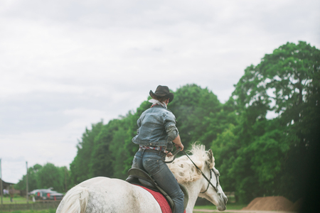Silhouette of a woman in cowboy hat riding a horse, horizontal