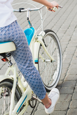 A young girl rides her bike, feet on the bicycle pedal close-up