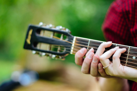 Boy and girl playing guitar, hands on the fretboard close-up