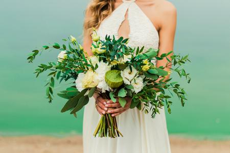 Hochzeit blüht Blumenstrauß in der Hand der Braut. Braut steht am Strand im Hochzeitskleid. Braut im Hochzeitskleid, das in der Hand Blumenblumenstrauß hält. Standard-Bild - 93748157