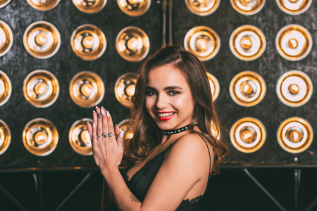 Young woman studio fashion portrait. Dark golden colors. Beautiful sexy woman on black background Standard-Bild