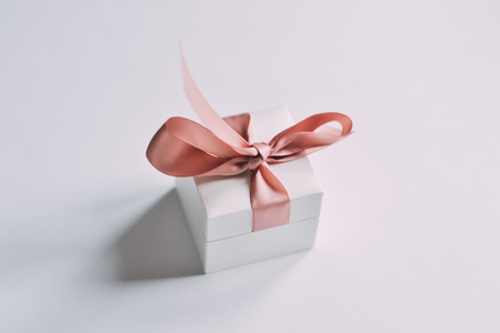 Close up shot a small gift wrapped with pink ribbon
