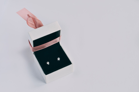 A silver earrings with precious stones in a small gift box Standard-Bild