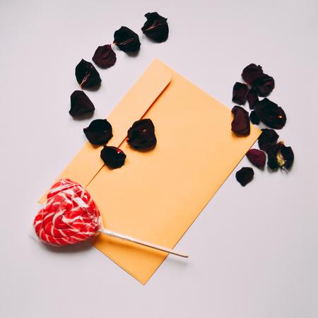 Valentinstagliebesbrief auf weißem Hintergrund. Orange Umschlag, rote Herzformsüßigkeit, rosafarbene Blumenblätter. Standard-Bild - 94742906