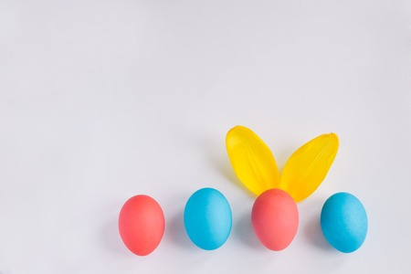 Happy Easter Concept. Big Colorful Eggs with Furry Bunny Ears isolated on white background. Top view with copy space Standard-Bild