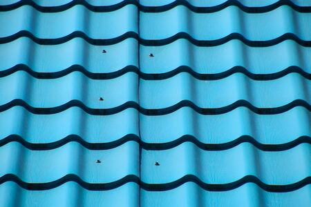 Turquoise metal tiles on the roof of the house. Modern roofing materials