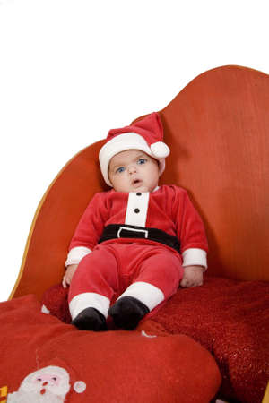 A baby dressed as Santa Claus sitting in a sleigh Stock Photo - 18461208