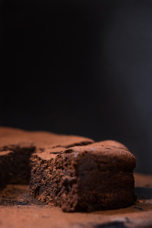 flourless chocolate cake: A close up slice of flourless chocolate cake on a dark background