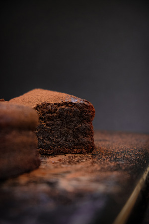 flourless chocolate cake: A close up slice of flourless chocolate cake on a dark background. Dark food photography. Free text space layout.