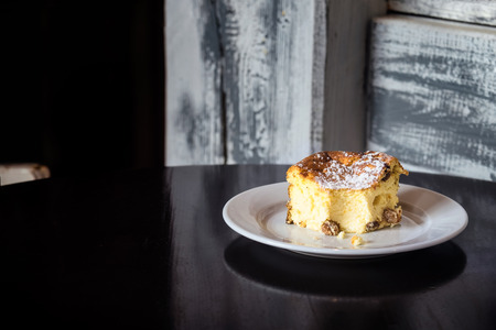 A slice of traditional Ukrainian cottage cheesecake on a dark wooden table