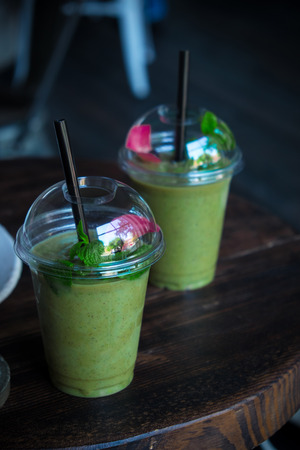 energizing: Two cups of green energizing veggie smoothie with avocado, spinach and mint. Decorated with rose petal. Wooden table and dark mood background. Stock Photo